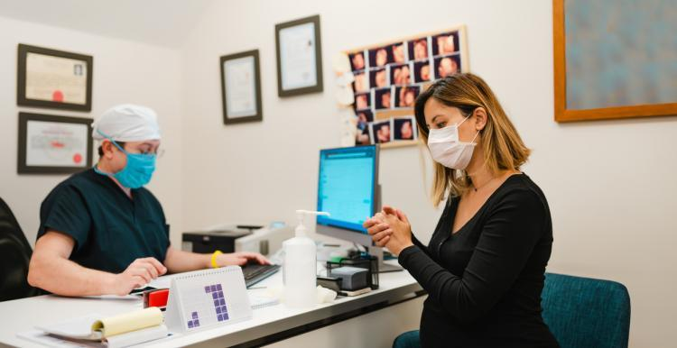 woman with face mask at the reception of doctors office