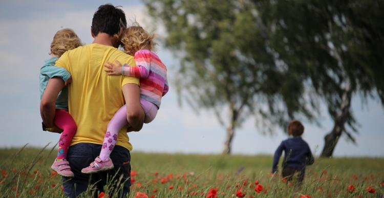 Father walking in park with kids in his arms