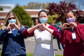3 care workers. Love sign with hands