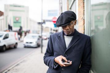 man on phone on the sidewalk