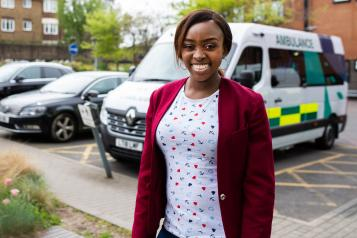 smiling woman standing in front of ambulance