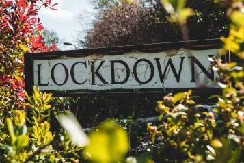 lockdown sign surrounded by plants