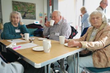 Elderly people sitting around a table drinking tea